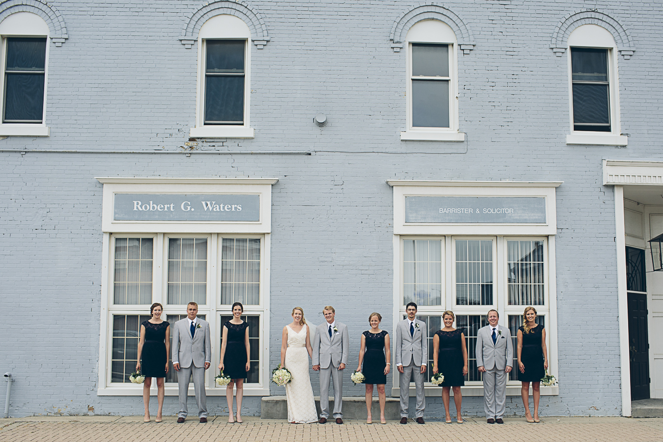 bridal party standing on sidewalk