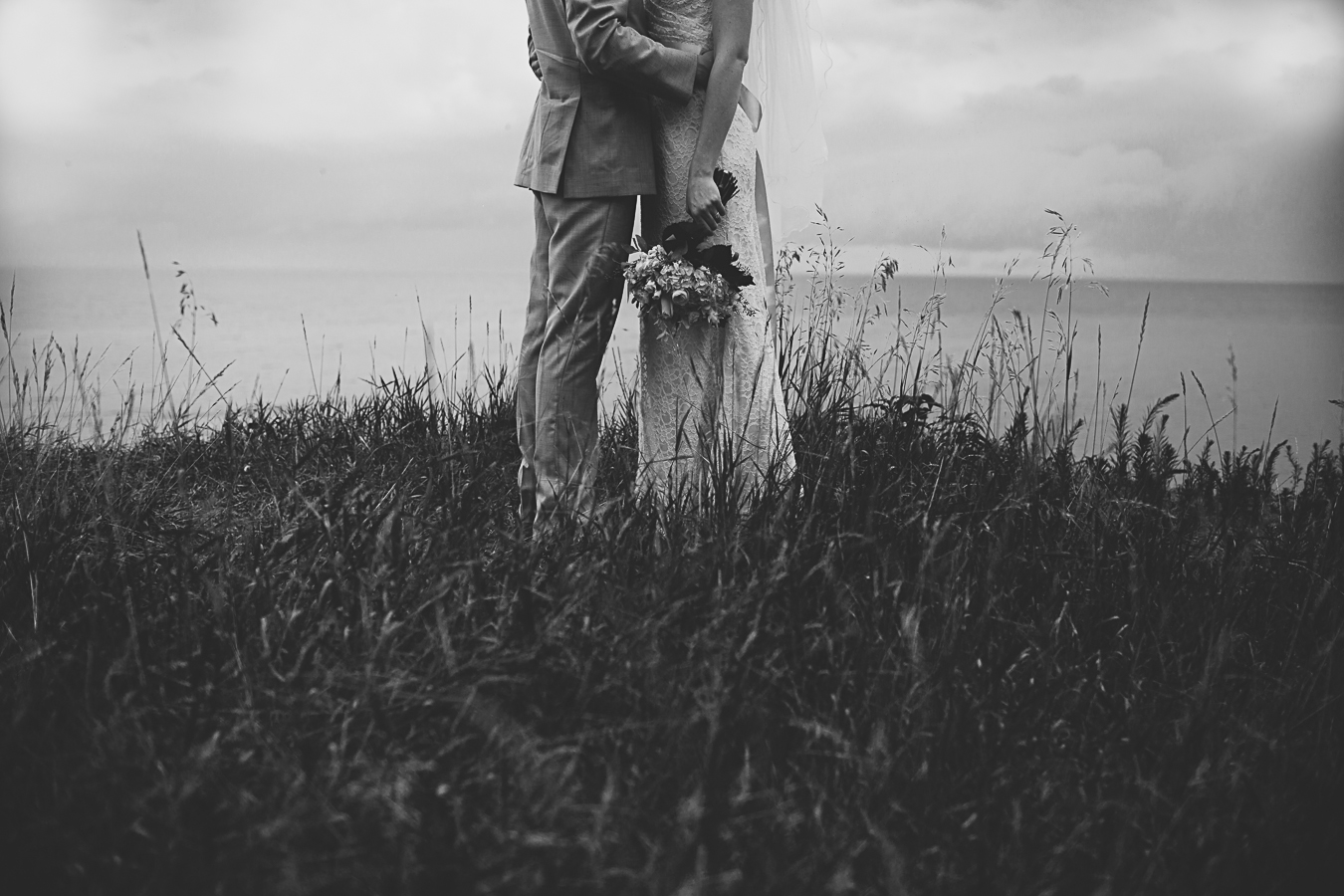 black and white portrait of bride and groom and boquet