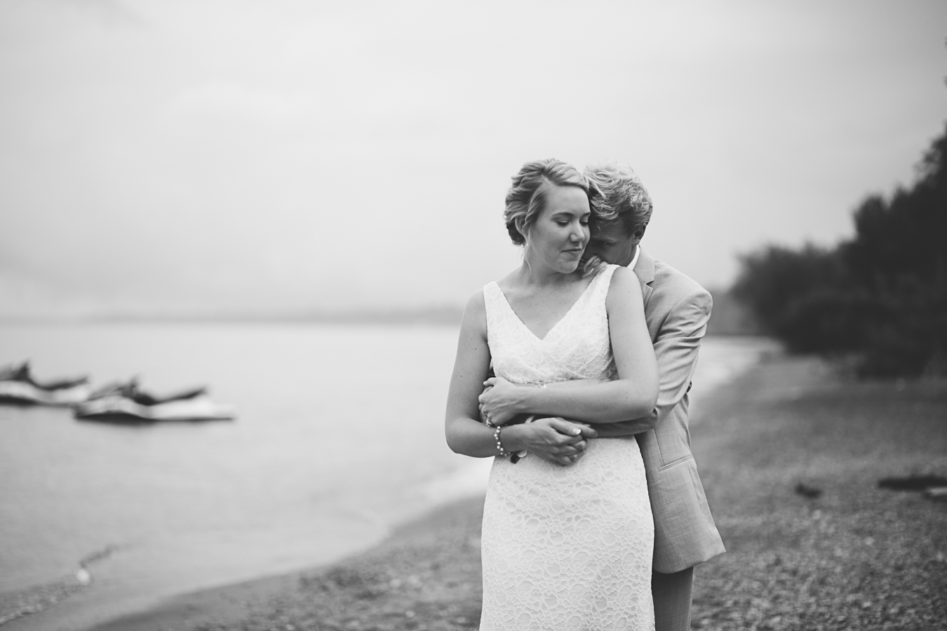 bride and groom snuggling on beach