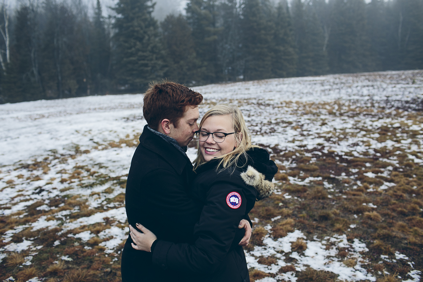 Couple hugging in cold snowy field