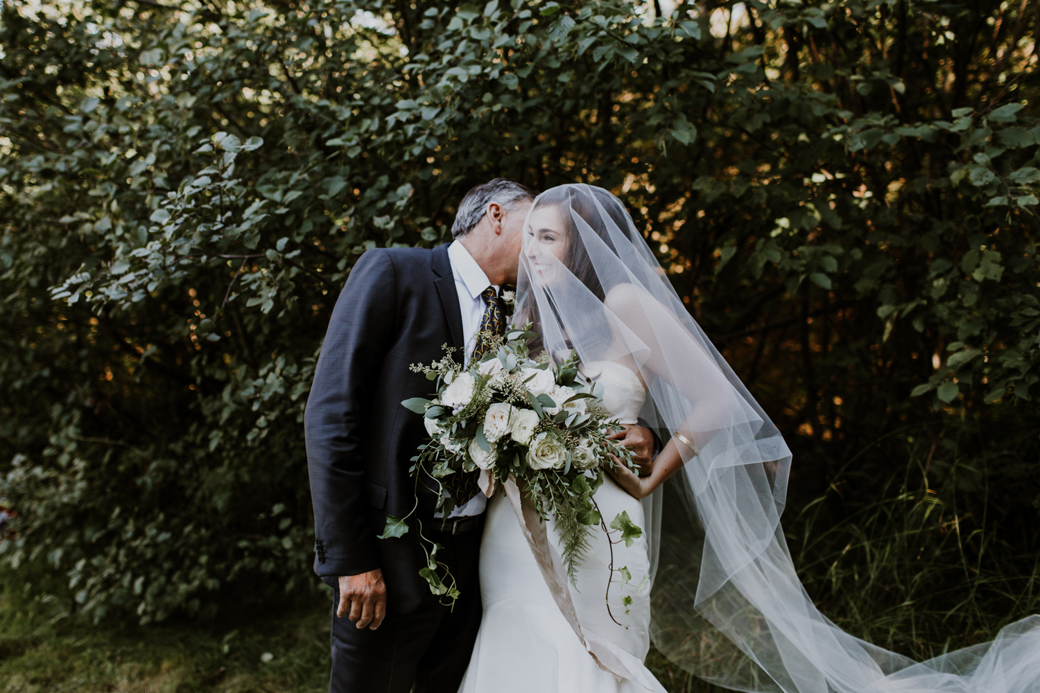 Father kissing bride before walking down isle