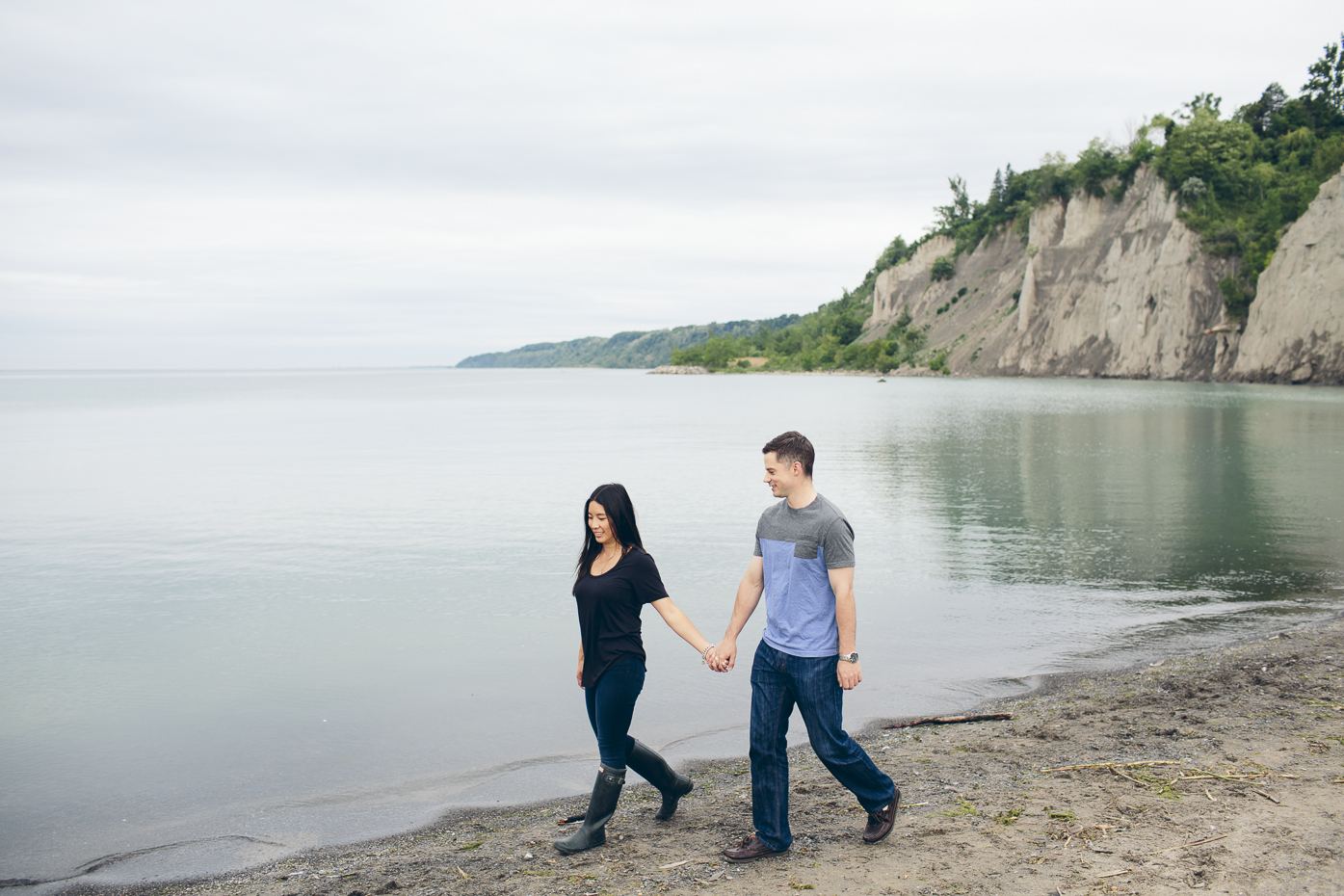 Engaged couple walking on the beach at the Scarborough Bluffs