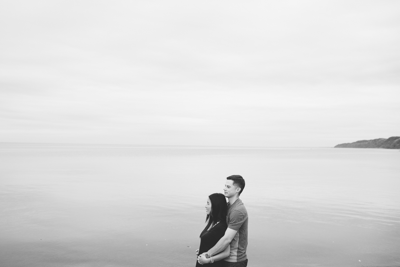 Black and white photograph of engaged couple. Early morning on Lake Ontario