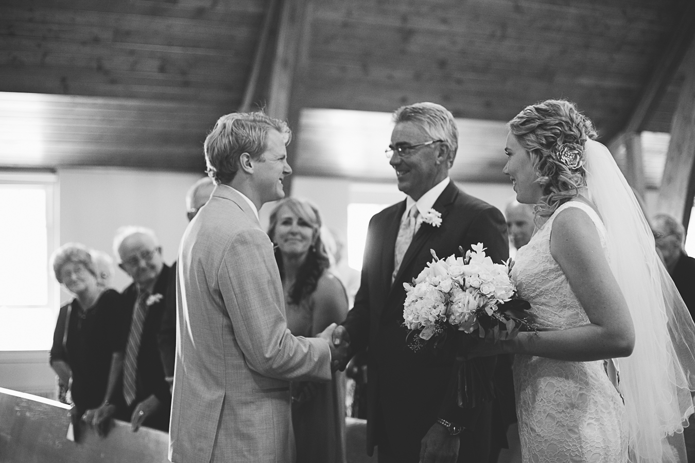 father passing daughter to groom at wedding