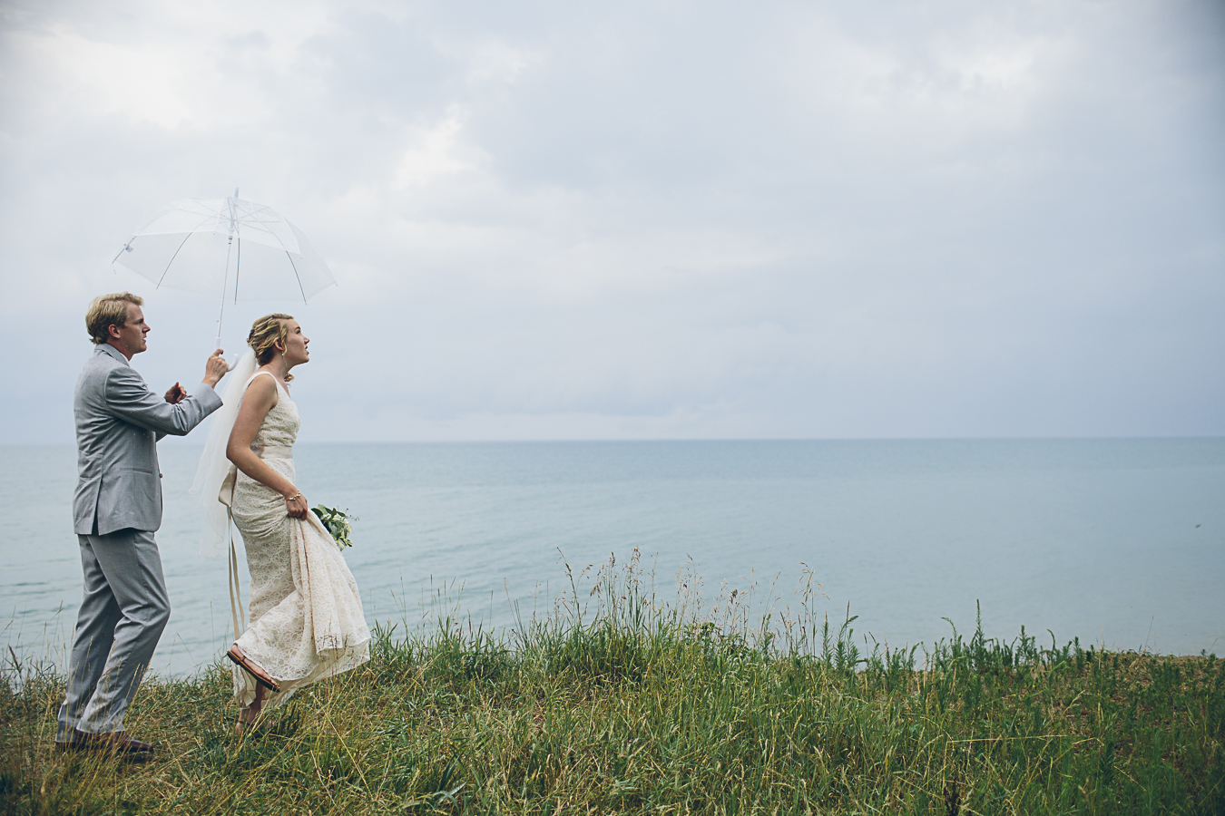 bride and groom with umbrella. On the shore of lake Huron