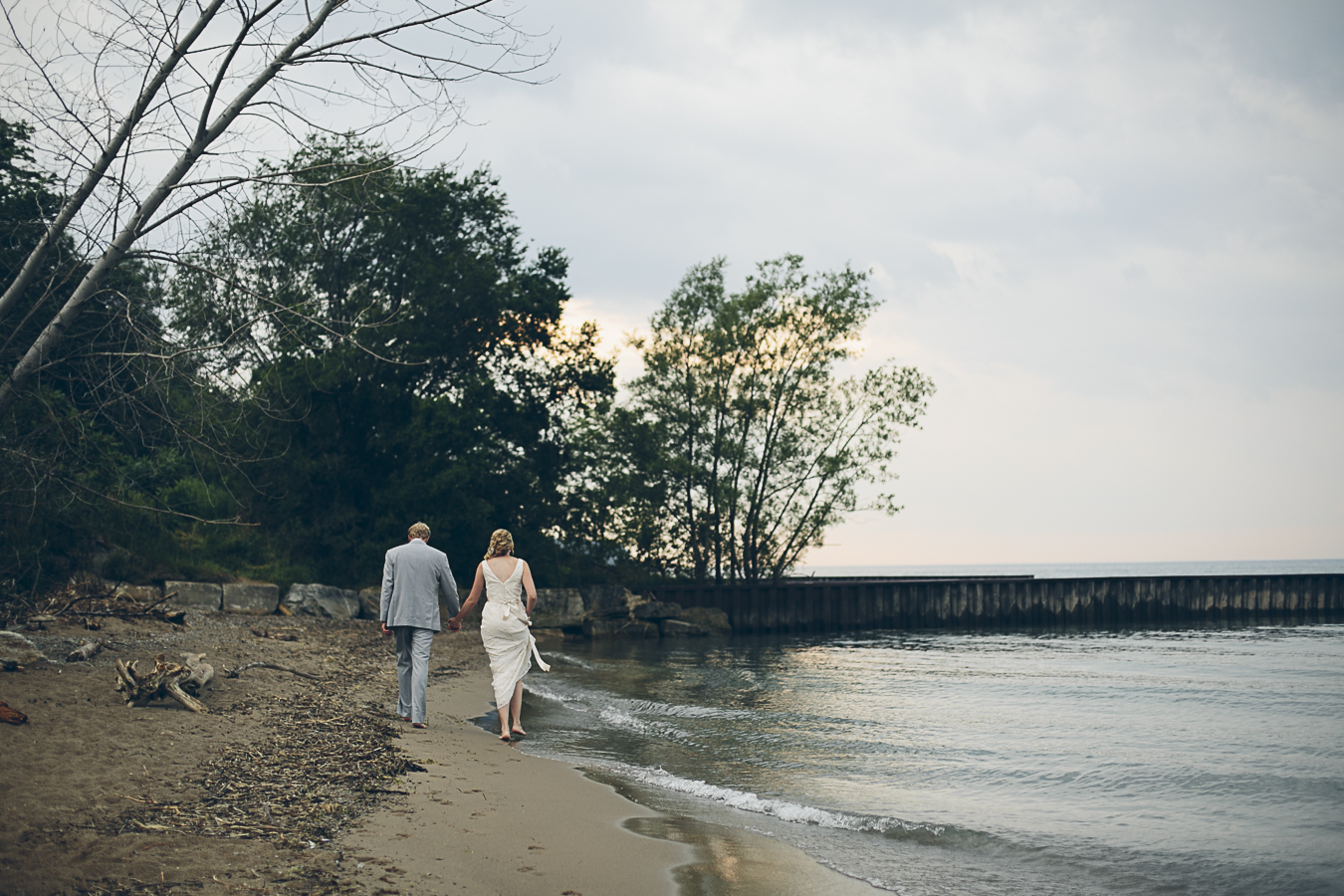 bride and groom walking on beach. Lake Huron