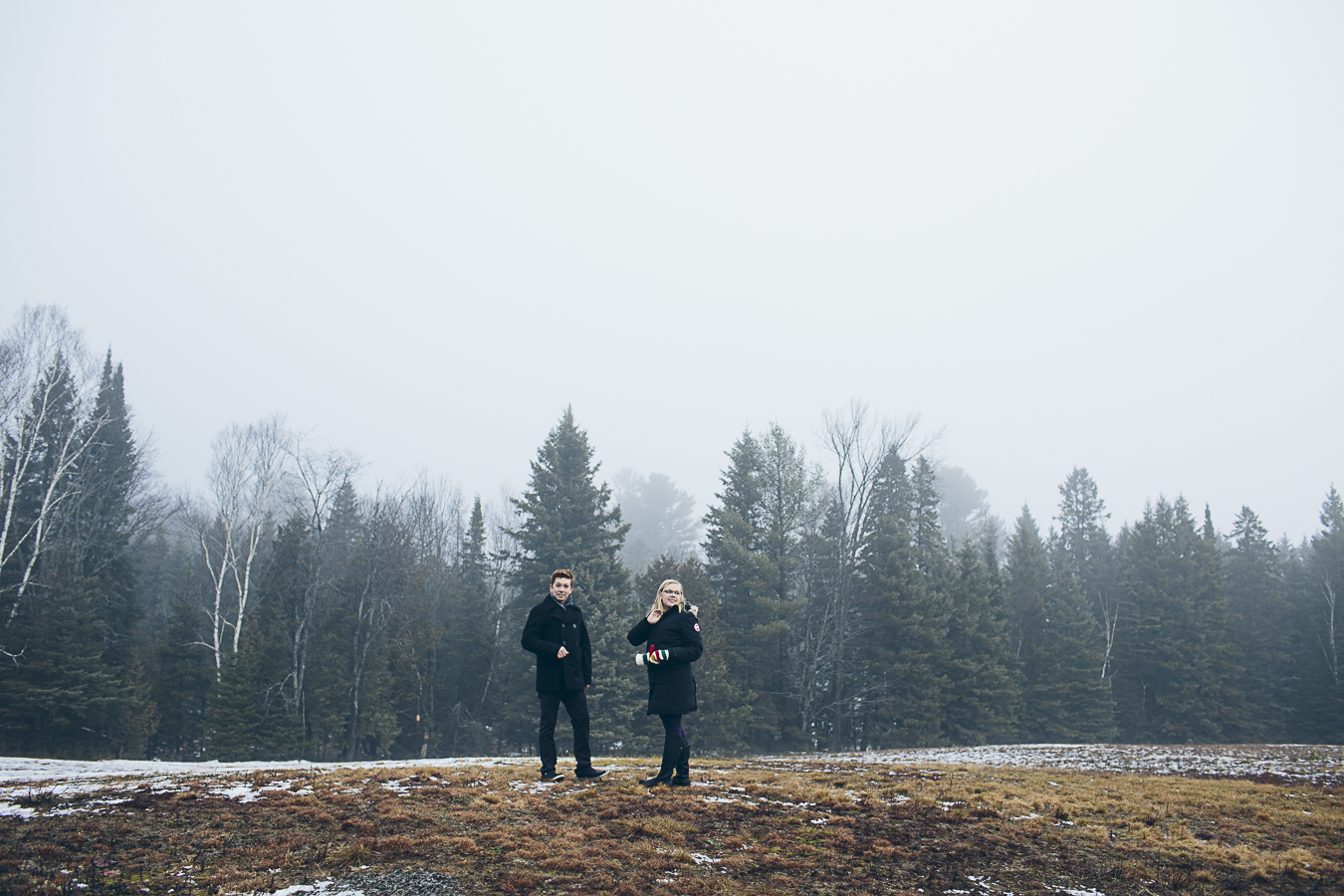 Couple standing in a snowy field in Haliburton Ontario