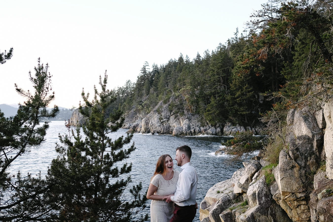 Pacific North West landscape with engaged couple laughing