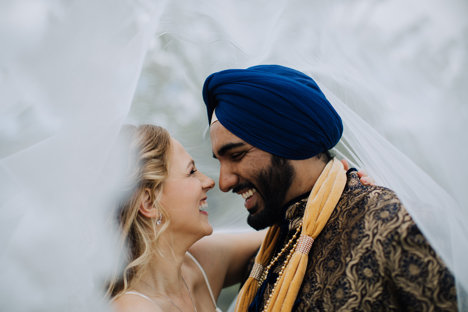 Portait of bride and groom. fusion wedding. Groom in traditional Sikh attire